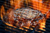picture of grill  - Delicious juicy rib eye steak on a barbecue grill with flames - JPG
