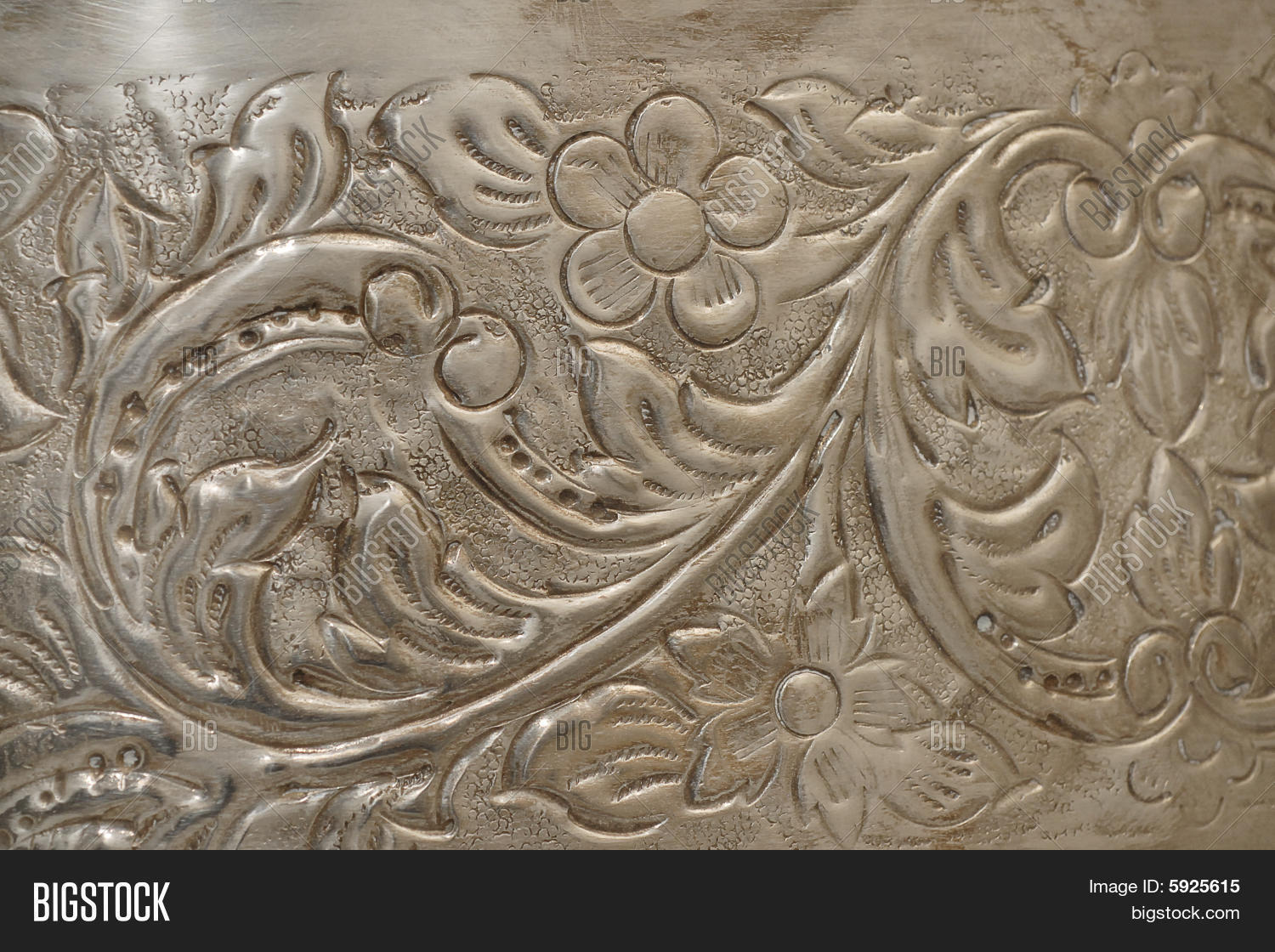 Metal relief carving on silver for background texture