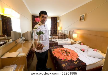 Bellboy with flower at hotel room