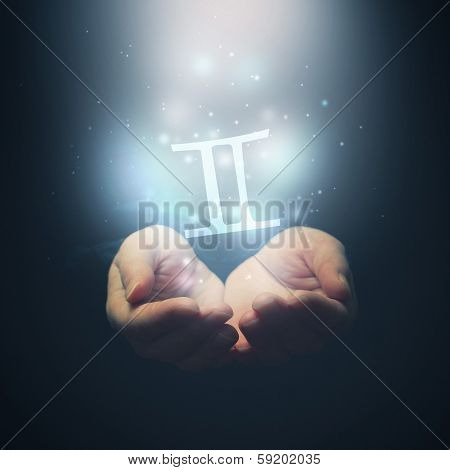 Female Hands Opening To Light And Holding Zodiac Sign For Gemini