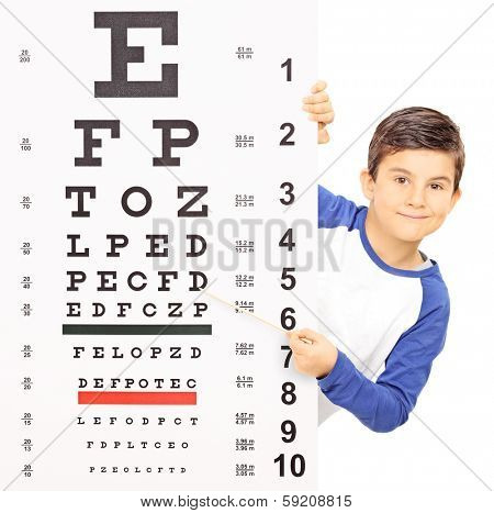 Little boy pointing on an eyesight test with stick isolated on white background, shot with tilt and shift lens