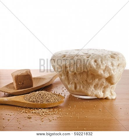 Rising Yeast Dough in bowl isolated on wooden table background
