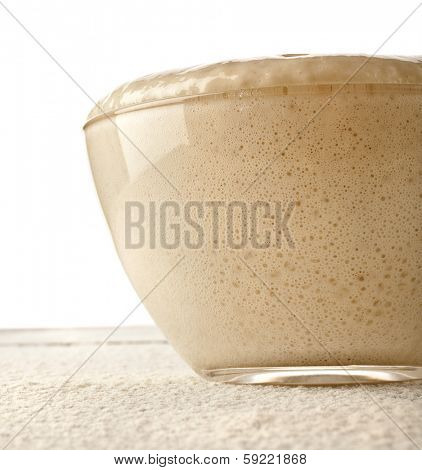 Rising Yeast Dough inglass  bowl close up on wooden table Isolated on White Background