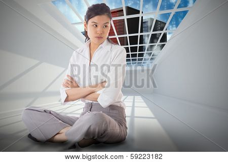 Annoyed businesswoman sitting with arms crossed against server tower seen through window