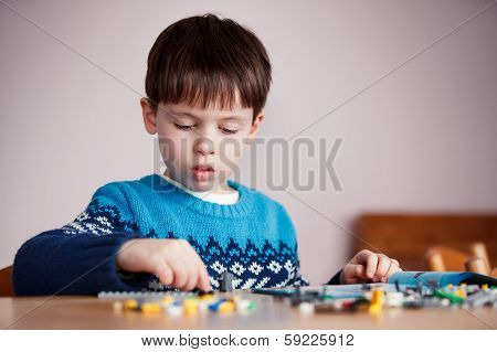 Five years old boy playing with building blocks