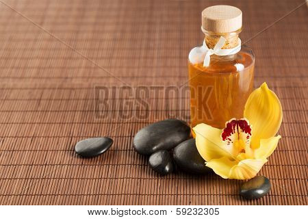 spa, health and beauty concept - closeup of essential oil, massage stones and orchid flower