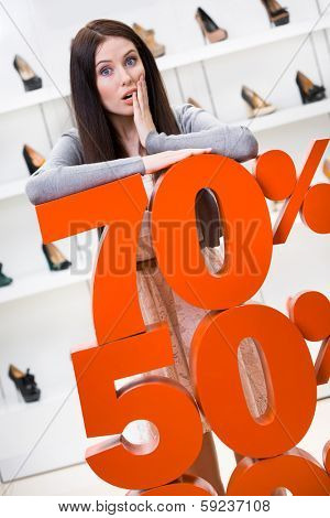 Woman showing the percentage of sales on footwear in the shopping center against the window case with pumps