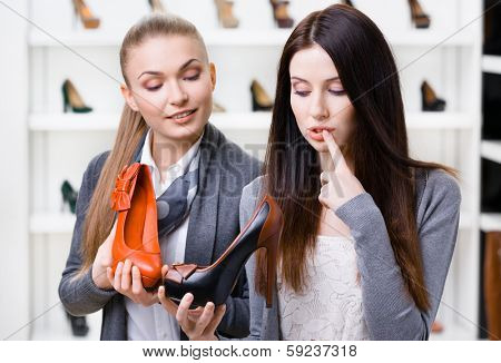 Shop assistant offers pumps for the female customer in the shopping center