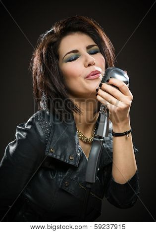 Half-length portrait of female rock musician wearing black jacket and holding mic on grey background. Concept of music and rave
