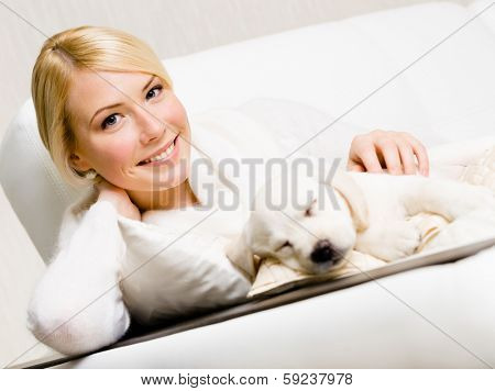 Woman sitting on the white leather sofa with sleeping on the pillow puppy of Labrador