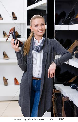 Woman with shoe in hand chooses pumps looking at the shelves with numerous pumps