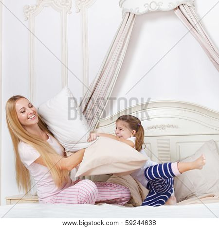 Family Having Pillow Fight In A Bedroom