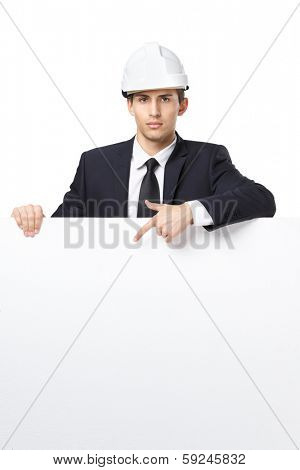 Businessman in white headpiece pointing hand gestures at copyspace, isolated on white. Concept of success and advertisement