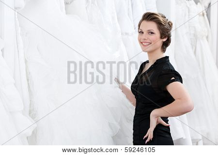 Shop assistant picks out the dress and hesitates should the bride try this particular dress or not