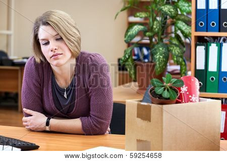 Dismissal - Frustrated Woman At A Desk With A Box With Things