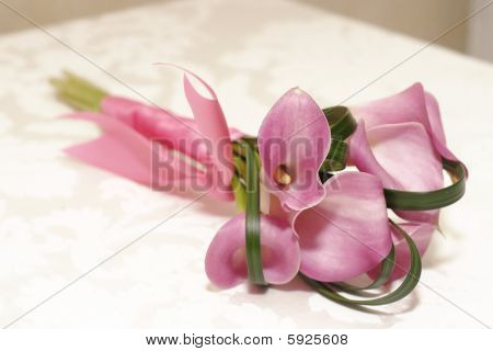 Wedding Bouquet of Lilly Flowers on table with pink ribbon