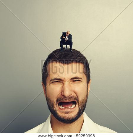 small angry boss screaming at big crying man over grey background