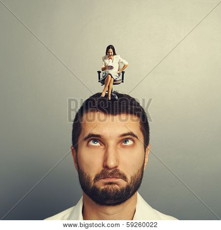 angry small woman screaming at stupid man over grey background
