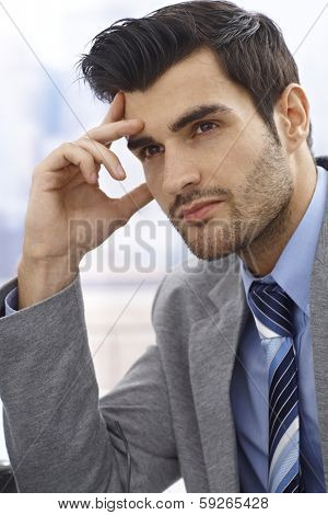 Closeup portrait of young businessman daydreaming, looking away.