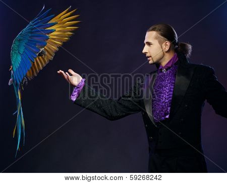 Young handsome brunette magician man in stage costume with his trained parrot