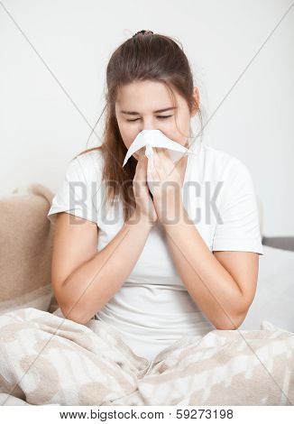 woman sitting on bed and sneezing