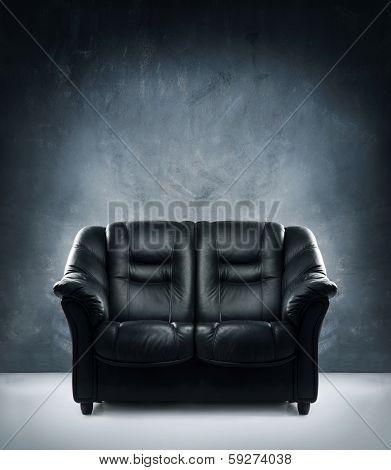 Black leather sofa in dramatic interior