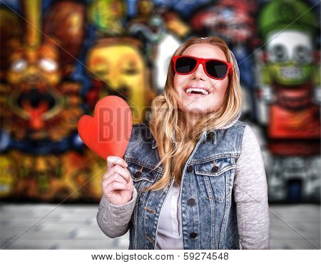 Funky teen girl in love, having fun outdoors, holding in hands  red heart as symbol of adolescents affection, urban lifestyle, stylish colorful graffiti on the wall behind young lady