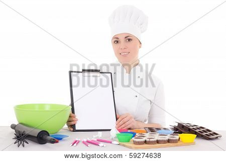Attractive Female Confectioner In Cook Uniform Sitting At The Kitchen With Clipboard Isolated On Whi