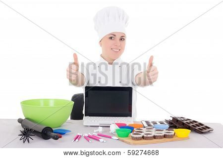 Female Confectioner In Cook Uniform Sitting At The Kitchen With Laptop With Copyspace Thumbs Up Isol