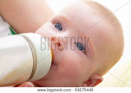 Bond little baby with blue eyes drinking bottle milk in mother arms