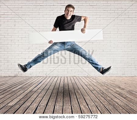 attractive young man jumping with a white banner on a room with white bricks wall and wood floor