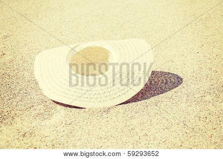 Droped straw summer hat on bright sand.