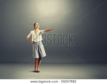 joyous woman pointing at empty copyspace in dark room