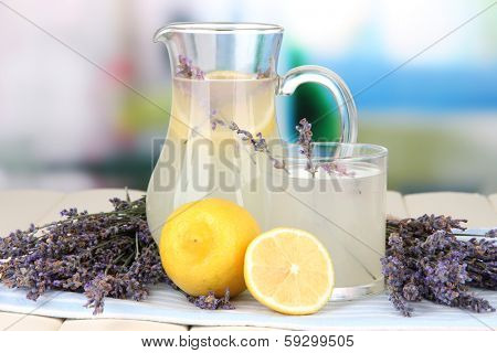 Lavender lemonade in glass jug, on napkin, on bright background