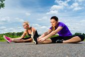 Urban sports - young women doing stretching exercises together before running in the greenfield on a