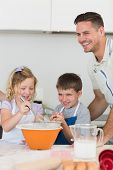 foto of flour sifter  - Happy children with father baking cookies at counter top in kitchen - JPG