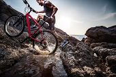 stock photo of ascending  - Athlete crossing rocky terrain with water barrier with his bicycle - JPG