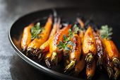 stock photo of dutch oven  - Oven baked baby carrots with thyme - JPG