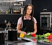 foto of apron  - Cheerful young woman in apron on modern kitchen cutting vegetables - JPG