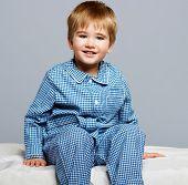 picture of pyjama  - Little boy wearing blue pyjamas in bed - JPG