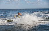 foto of waverunner  - strong man drive on the jetski above the water - JPG