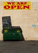 foto of dumpster  - large green dumpster lid open with a pink wall behind it and a WE ARE 0PEN sign above it - JPG