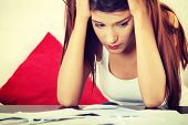 image of overwhelming  - A young beautiful woman stressed because of bills - JPG