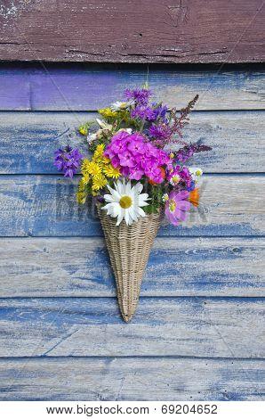 Beautiful  Flowers In Wicker Basket On Old Wooden Wall