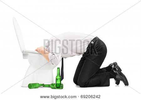 Drunk man throw up in a toilet with empty beer bottles next to him isolated on white background