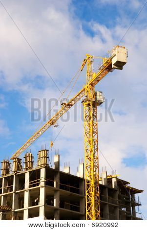 Crane Near Building On Cloudly Sky Background