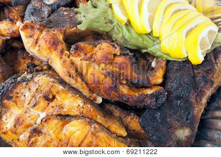 Barbecue of fish decorated with lemon wedges.