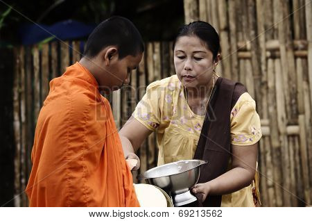 An unidentified women Gives food offerings to a Buddhist monk