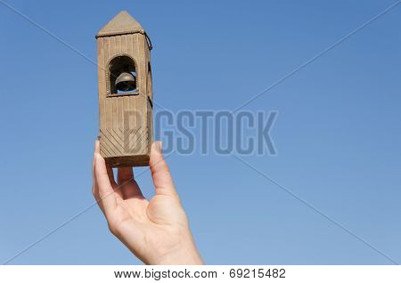 Hand Hold Belfry Miniature On Blue Sky Background