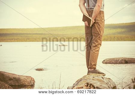 Young Man With Book Standing Outdoor With Lake On Background Summer Vacations And Lifestyle Concept